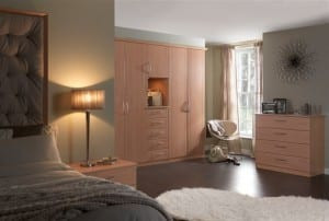 Beech finished fitted bedroom with wardrobe run featuring a range of door options, bedside and drawer unit