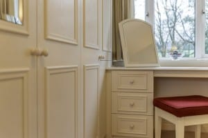 Close up of cream fitted wardrobe run and adjoining dressing table with freestanding mirror and stool