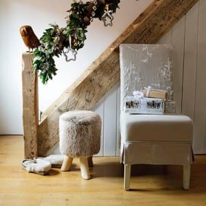 Holly-decked country style staircase with textured chair and footstool.
