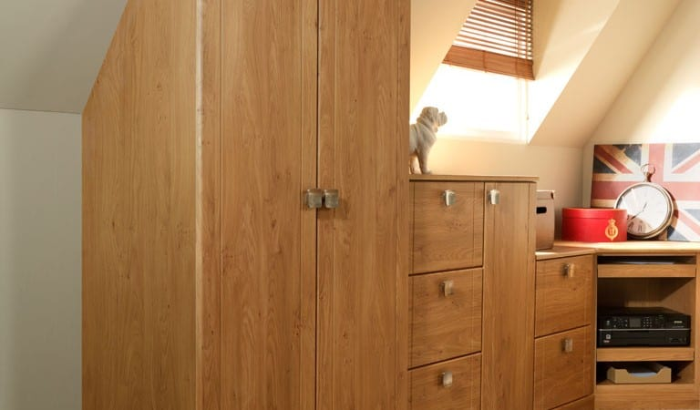 Sorrento range in a pipi oak finish; wardrobe fitting seamlessly against a sloping ceiling