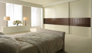 Textured sliding wardrobes in an ivory ash finish with contemporary copper panelling