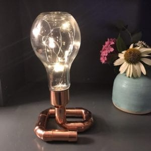Exposed light bulb in a copper light stand